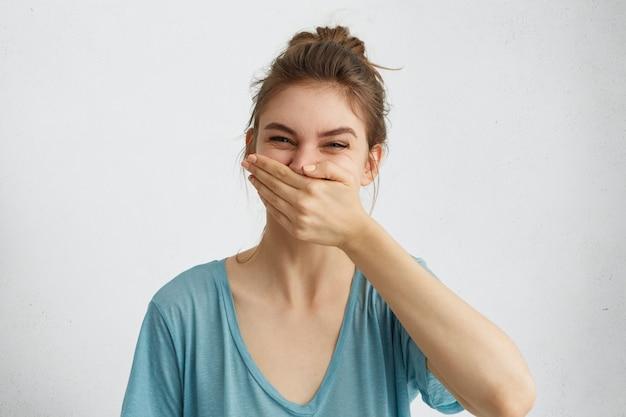 Mulher positiva rindo enquanto tem bom humor durante o tempo livre, tentando controlar suas emoções, cobrindo a boca com a mão.