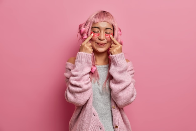 Mulher positiva satisfeita tem cabelos longos rosados, faz penteado encaracolado com bobes, indica manchas de beleza, fica de olhos fechados usa suéter quente