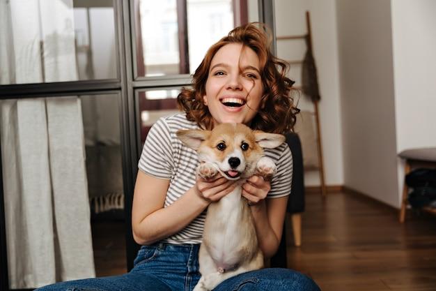 Mulher positiva se senta no chão na sala de estar e com sorriso brinca com seu amado cachorro.