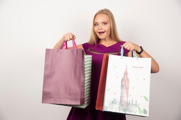 Mulher positiva segurando sacolas coloridas.