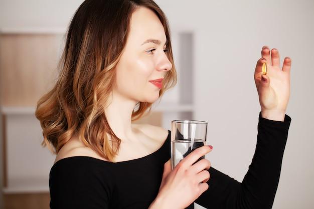 Mulher positiva sorridente feliz comendo a pílula e segurando o copo de água na mão, em sua casa
