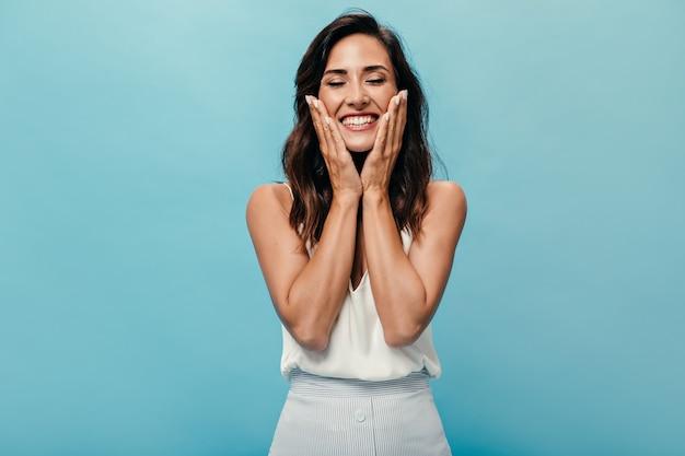 Mulher positiva sorrindo com os olhos fechados sobre fundo azul. linda senhora de cabelos escuros em roupa leve se alegra e posa para a câmera.