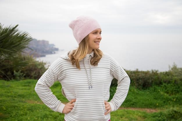 Mulher positiva, vestindo roupas esportivas e relaxante ao ar livre