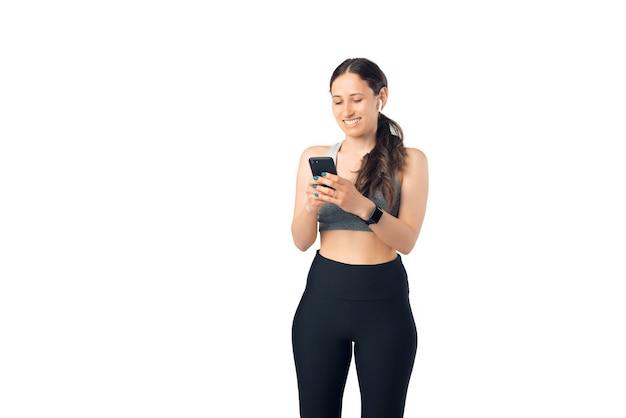 Mulher positiva vestindo roupas esportivas está configurando seu player para ouvir música.