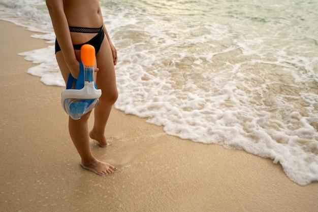 Mulher, praia, e, ela, segura, um, scuba, dirigindo, óculos proteção, em, a, litoral, em, a, manhã