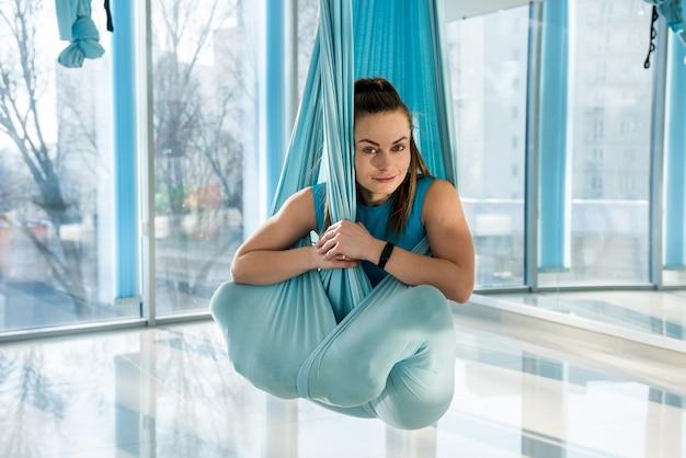 Mulher pratica ioga aérea na rede. tipo de esporte anti-gravidade relaxante. saúde, voar o conceito de ioga.