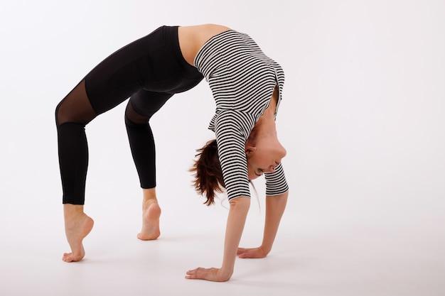 Mulher pratica ioga em caneleiras pretas sobre fundo branco isolado. posição da ponte. dia da ioga