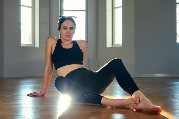 Mulher pratica ioga em uma sala de fitness ao amanhecer. concentração, sol bonito, alongamento, estilo de vida saudável.