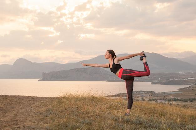 Mulher pratica ioga nas montanhas no oceano.