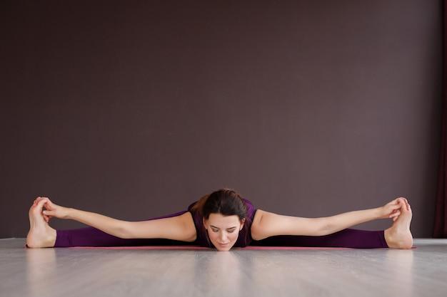 Mulher pratica ioga no sportswear. divide e se estende em casa. relaxamento e meditação, asana. dia internacional da ioga