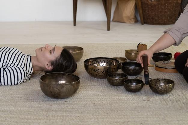 Mulher pratica terapia de som de taças cantantes para recuperação da ansiedade e alívio do estresse em casa