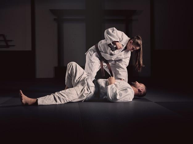 Mulher praticando artes marciais com seu treinador em quimonos