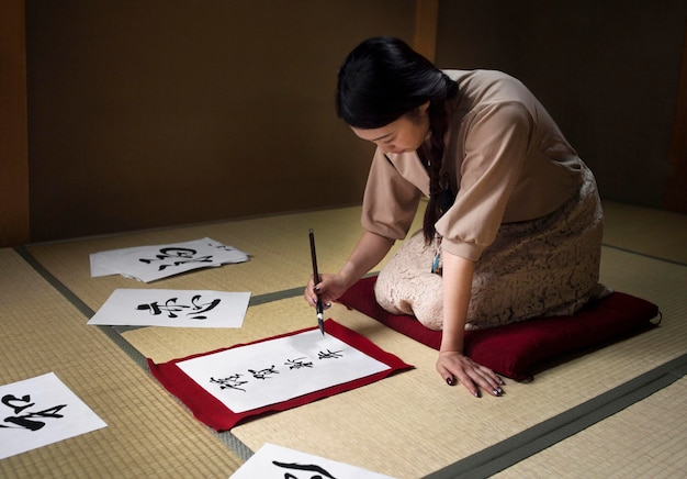 Mulher praticando caligrafia japonesa dentro de casa
