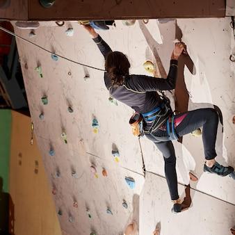 Mulher praticando escalada em uma parede de pedra dentro de casa