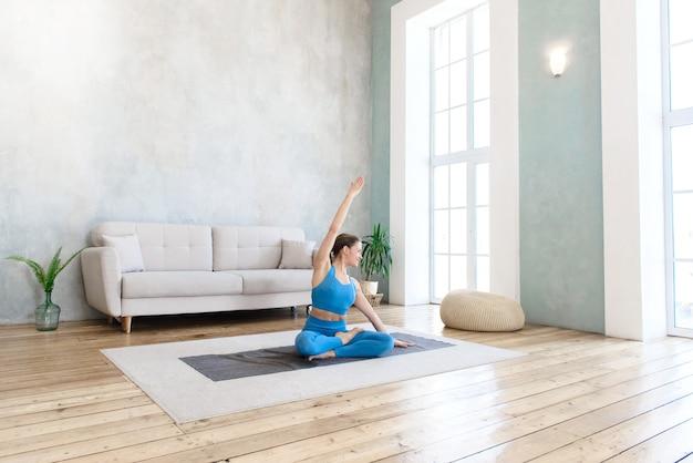Mulher praticando esportes em casa praticando ioga e alongamento em posição de lótus