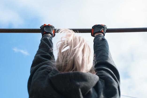 Mulher praticando flexões no bar do lado de fora. treino ao ar livre. estilo de vida ativo. vista traseira, foco nas mãos