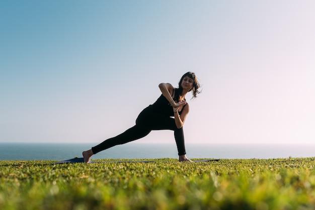 Mulher praticando ioga, alonga o corpo com um fundo de céu e mar.