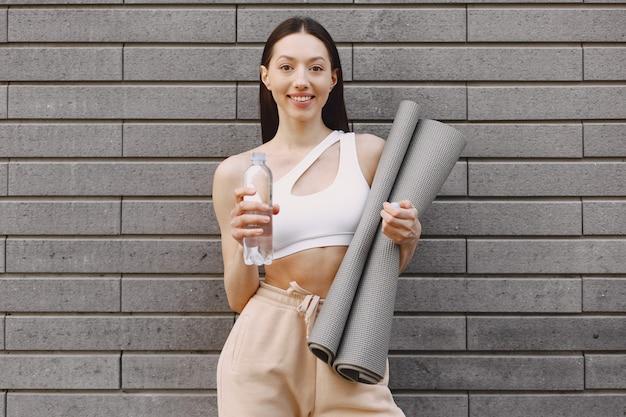 Mulher praticando ioga avançada contra uma parede urbana escura