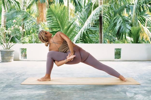 Mulher praticando ioga avançada em tapete orgânico