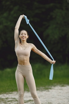 Mulher praticando ioga avançada em uma praia de verão
