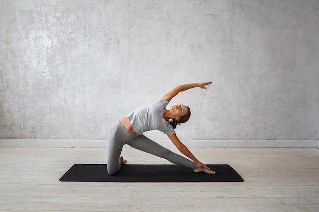 Mulher praticando ioga avançada.
