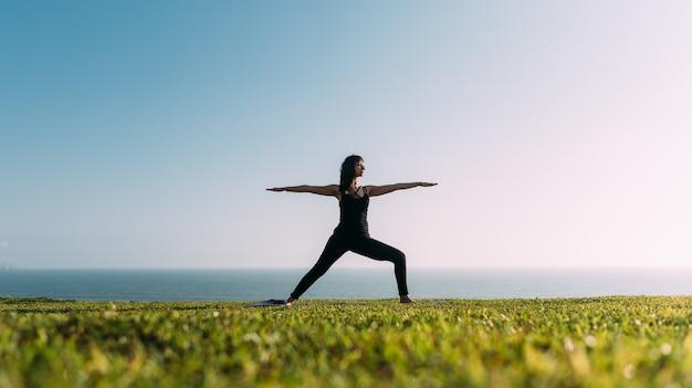 Mulher praticando ioga com os braços estendidos sobre um fundo de céu e mar. copie o espaço