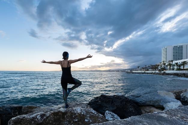 Mulher praticando ioga de frente para o mar em um dia nublado