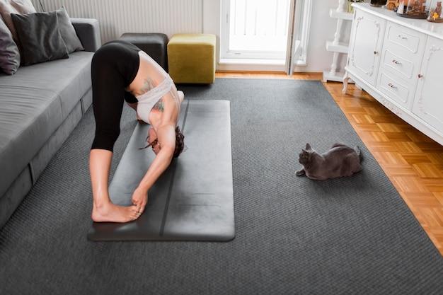 Mulher praticando ioga e gato em casa com vista lateral