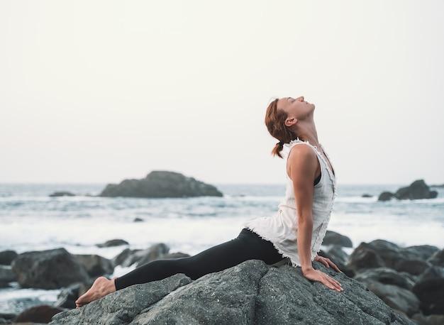 Mulher praticando ioga e meditação na bela praia selvagem