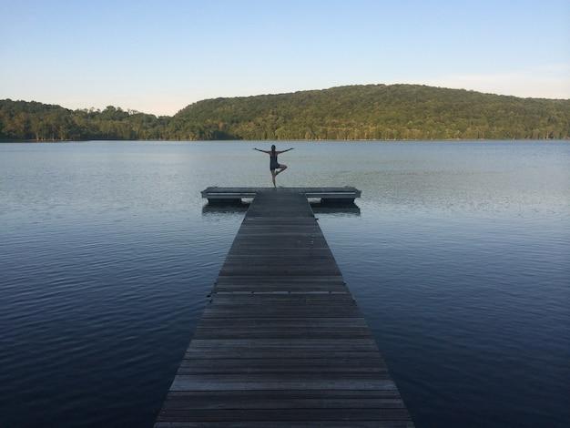 Mulher praticando ioga e meditando à beira do lago no fundo do verão