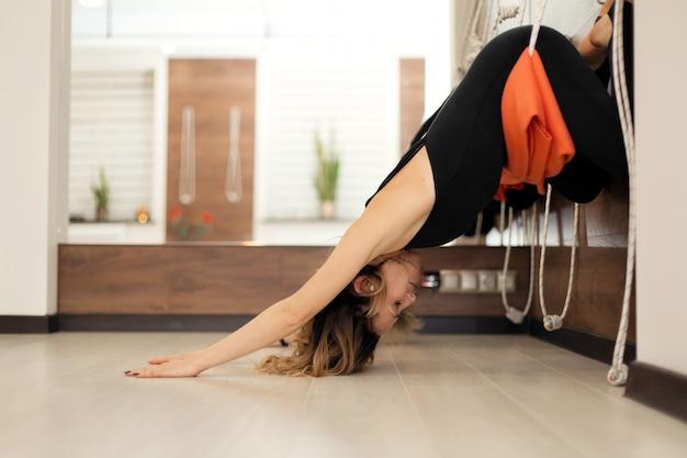 Mulher praticando ioga em cordas, estendendo-se no ginásio. f