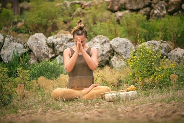 Mulher praticando ioga em pose de lótus na natureza