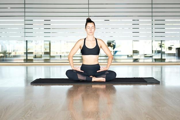 Mulher praticando ioga em uma academia, se exercitando em uma roupa esporte preta, fazendo exercícios de meditação.