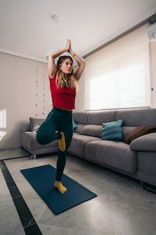 Mulher praticando ioga em uma esteira em sua sala de estar em casa