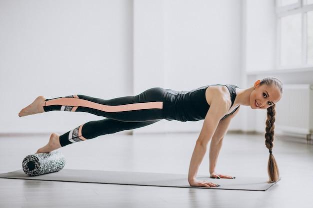 Mulher praticando ioga em uma esteira
