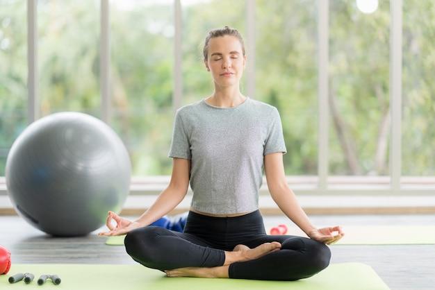 Mulher praticando ioga na academia