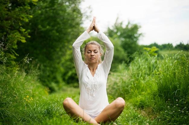Mulher praticando ioga na natureza