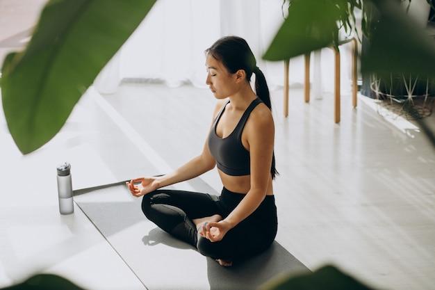 Mulher praticando ioga no colchonete em casa