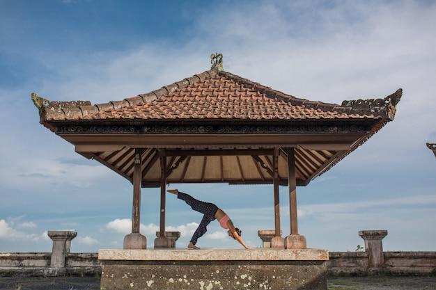 Mulher praticando ioga no gazebo balinesse tradicional