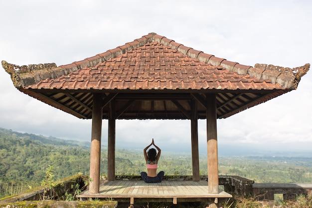 Mulher praticando ioga no gazebo balinesse tradicional.