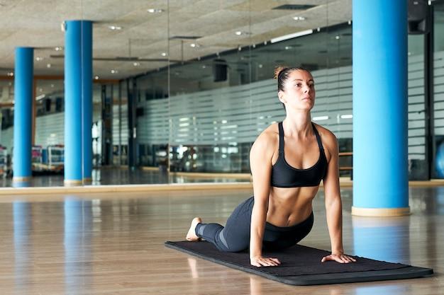 Mulher praticando ioga ou pilates em uma academia, exercitando-se em roupas esportivas, fazendo extensão das costas. bhujangasana