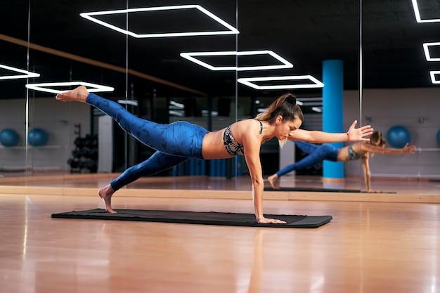Mulher praticando ioga ou pilates em uma academia, se exercitando em uma roupa esportiva azul, fazendo pose de cachorro-pássaro.
