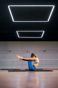 Mulher praticando ioga ou pilates em uma academia, se exercitando em uma roupa esportiva azul, fazendo pose de navasana