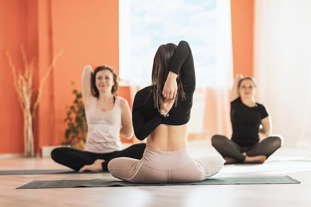 Mulher praticando ioga realiza um treino para seus alunos no estúdio sentada em esteiras na posição de lótus e realizando o exercício gomukhasana dando as mãos atrás das costas