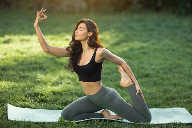 Mulher praticando ioga, realizando ioga-asanas. jovem atraente magro em body relaxante e