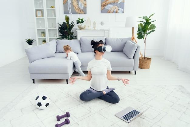 Mulher praticando ioga usando fone de ouvido com tecnologia vr na aula online em casa.