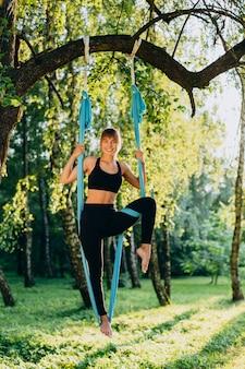 Mulher praticando ioga voar no parque ao ar livre em pose de pé olhando para a câmera