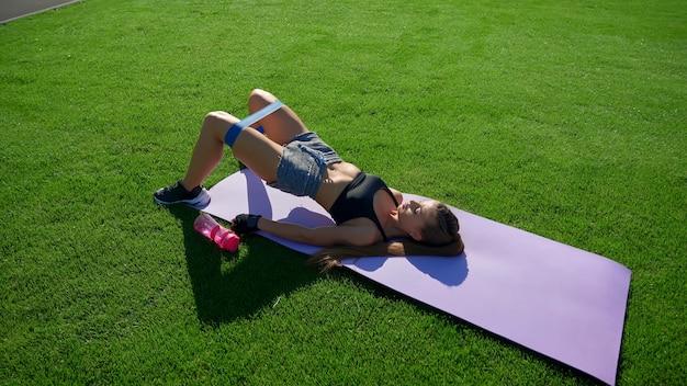 Mulher praticando levantamento de bunda em bridge usando banda de resistência