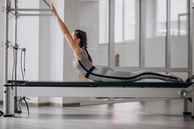 Mulher praticando pilates em um reformador de pilates