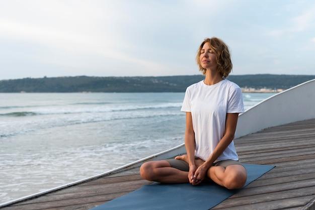 Mulher praticando pose de ioga perto do mar